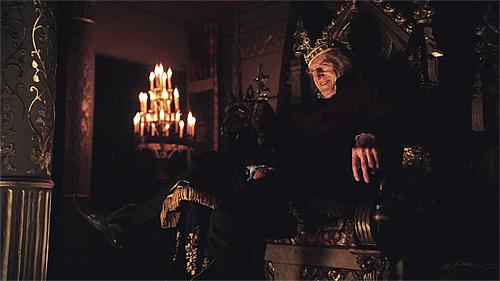 O ''velho'' Will Sommers em The Tudors, sentado no trono real com a coroa.